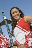 Lächelnde Cheerleaderholdingtrophäe Stockfoto