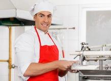 Lächelnde Chef-Standing By Ravioli-Teigwaren-Maschine Lizenzfreie Stockbilder