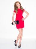 Lächelnde dünne Frau im roten Kleid, das Geldbeutel hält Lizenzfreie Stockfotografie