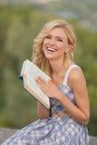 Lächelnde Dame mit einem Buch draußen Stockfoto