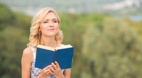 Lächelnde Dame mit einem Buch draußen Stockfotos