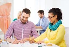Lächelnde Designer, die Skizzen im Büro zeichnen Lizenzfreie Stockbilder