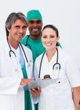 Lächelnde Doktoren und Chirurg, die Kenntnisse nehmen stockbilder