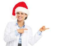 Lächelnde Doktorfrau in Sankt-Hut zeigend auf Kopienraum Stockfotos