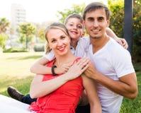 Lächelnde dreiköpfige Familie auf grüner Wiese stockfotos