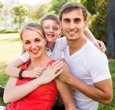 Lächelnde dreiköpfige Familie auf grüner Wiese lizenzfreie stockbilder