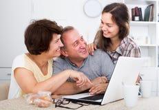 Lächelnde dreiköpfige Familie, die Dokumente auf Laptop sucht Lizenzfreie Stockfotografie