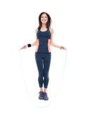 Lächelnde Eignungsfrau, die mit Springseil springt Stockfotografie