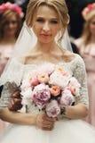Lächelnde elegante blonde Braut mit rosafarbenem Hochzeitsblumenstrauß im Weiß Stockfotografie