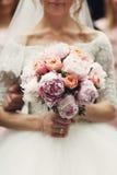 Lächelnde elegante blonde Braut mit rosafarbenem Hochzeitsblumenstrauß im Weiß Lizenzfreies Stockfoto