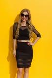 Lächelnde elegante blonde Frau im schwarzen Kleid Stockfotografie