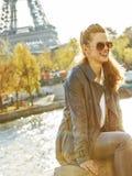 Lächelnde elegante Frau, die auf dem Geländer in Paris, Frankreich sitzt lizenzfreie stockfotografie