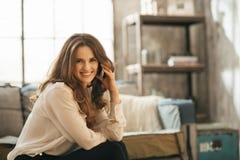 Lächelnde elegante Frau, die auf Sofa und Unterhaltungssmartphone sitzt lizenzfreies stockfoto
