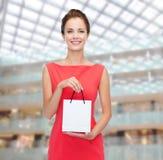 Lächelnde elegante Frau im Kleid mit Einkaufstasche Stockfotografie