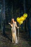 Lächelnde elegante Frau mit Ballonen im Holz lizenzfreie stockfotografie