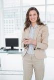 Lächelnde elegante Geschäftsfrauversenden von sms-nachrichten im Büro Stockbild