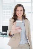 Lächelnde elegante Geschäftsfrauversenden von sms-nachrichten im Büro Lizenzfreie Stockfotos