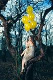 Lächelnde elegante Modefrau mit Ballonen im Wald lizenzfreies stockbild