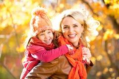 Lächelnde Elternteil- und Kinderfamilie zusammen gehend im Freien im Fall Stockbild