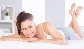 Lächelnde entspannte junge Frau, die im Bett liegt Stockfotografie