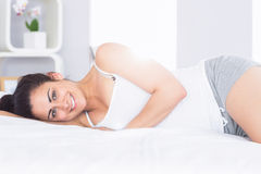 Lächelnde entspannte junge Frau, die im Bett liegt Stockfotos