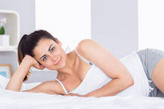 Lächelnde entspannte junge Frau, die im Bett liegt Lizenzfreie Stockbilder