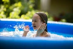 Lächelnde entzückende sieben Jahre alte Mädchen, die Spaß im aufblasbaren Pool spielen und haben lizenzfreies stockbild