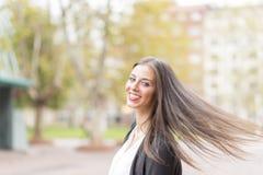 Lächelnde erfolgreiche Geschäftsfrau, die Kamera in der Straße betrachtet Lizenzfreies Stockfoto