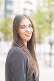 Lächelnde erfolgreiche Geschäftsfrau, die Kamera in der Straße betrachtet Lizenzfreie Stockfotografie