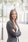 Lächelnde erfolgreiche Geschäftsfrau, die Kamera in der Straße betrachtet Lizenzfreie Stockfotos