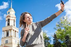 Lächelnde europäische Frau der Junge, die Selbstporträtphoto mit leicht behandelter Kamera gegen Glocketurm der Kirche in Russlan Stockbilder