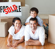 Lächelnde Familie auf dem Fußboden, nachdem Haus gekauft worden ist lizenzfreie stockbilder