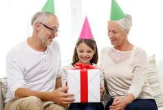 Lächelnde Familie in den Parteihüten mit Geschenkbox zu Hause Lizenzfreies Stockfoto