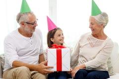 Lächelnde Familie in den Parteihüten mit Geschenkbox zu Hause Lizenzfreie Stockbilder