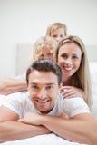 Lächelnde Familie, die auf Bett liegt Lizenzfreie Stockfotografie