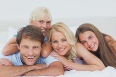 Lächelnde Familie, die auf Bett liegt Lizenzfreies Stockfoto