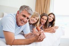Lächelnde Familie, die auf dem Bett liegt Stockbilder