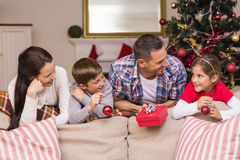 Lächelnde Familie, die auf der Couch sich lehnt Lizenzfreies Stockfoto