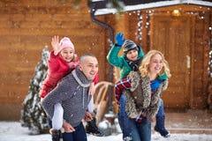 Lächelnde Familie, die auf Winterurlaub genießt lizenzfreie stockfotos