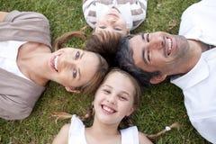 Lächelnde Familie, die draußen liegt Stockfotos