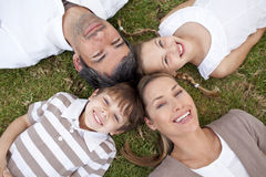 Lächelnde Familie, die in einem Park liegt Lizenzfreie Stockfotos