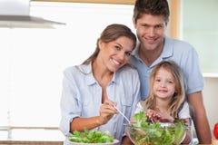 Lächelnde Familie, die einen Salat zubereitet Lizenzfreies Stockfoto