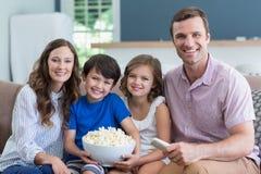 Lächelnde Familie, die fernsieht und zu Hause Popcorn im Wohnzimmer isst Stockfotografie