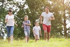 Lächelnde Familie, die zusammen über Sommer-Feld läuft Stockfotos