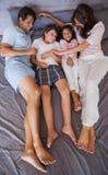 Lächelnde Familie, die zusammen auf Bett liegt Stockfoto