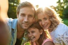 Lächelnde Familie, die zusammen ein selfie draußen nimmt stockfotografie