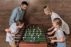 Lächelnde Familie, die zusammen foosball spielt lizenzfreie stockfotografie