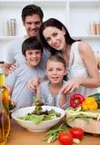 Lächelnde Familie, die zusammen kocht Lizenzfreie Stockfotos