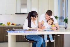 Lächelnde Familie, die zusammen zu Hause in Küche zeichnet stockbilder