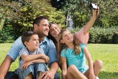 Lächelnde Familie in einem Park, der Fotos macht Stockfoto